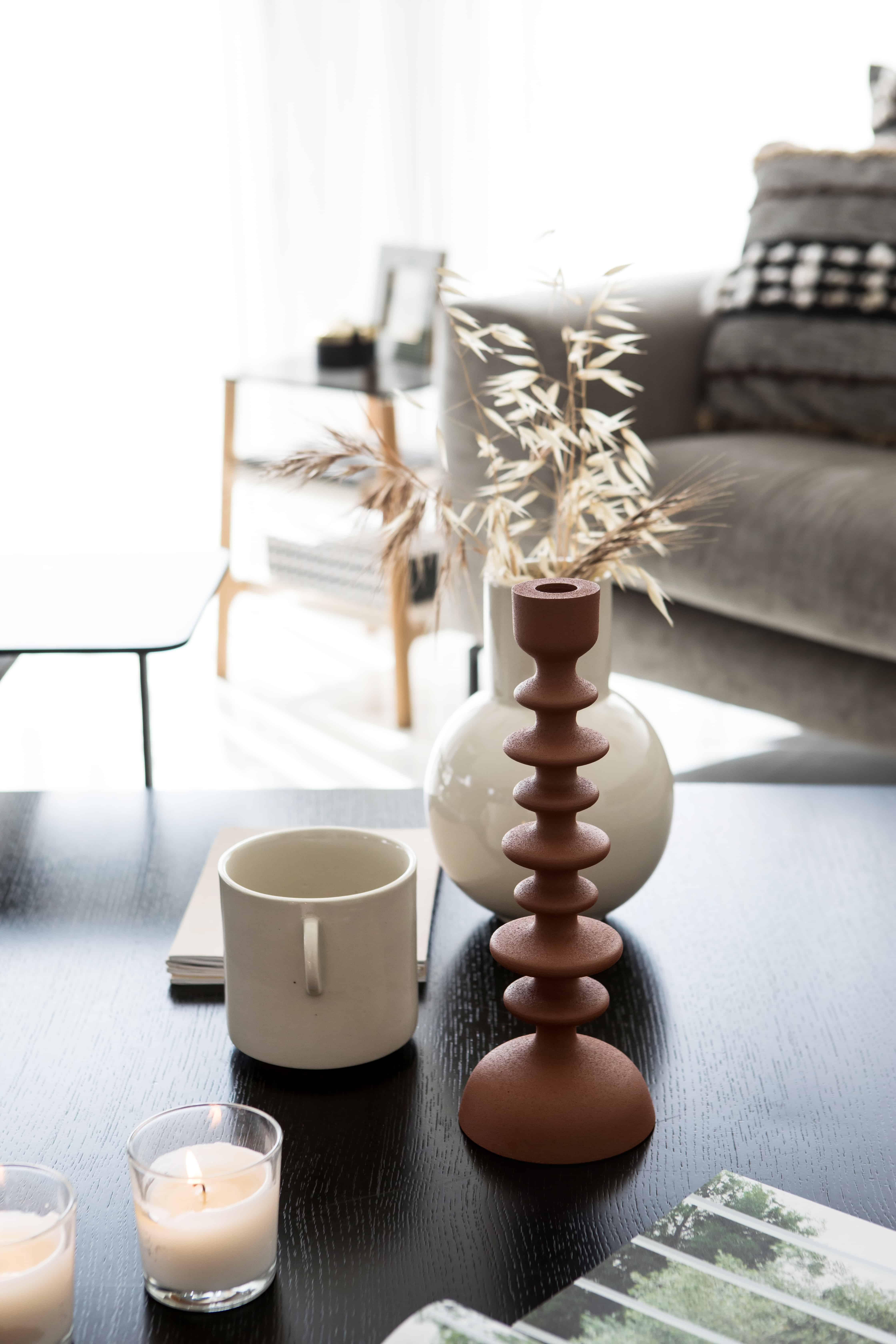 תקריב שולחן סלון ,פמוטים וכד עם עשבים עיצוב לירז בוקעי